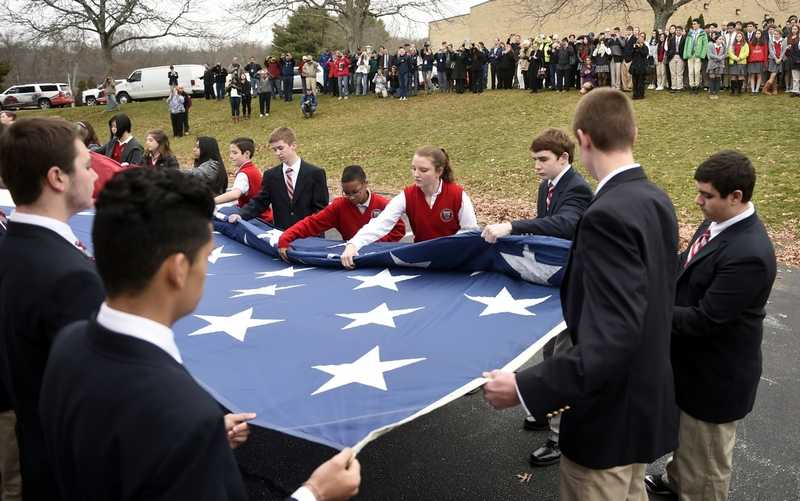St. Bernard School students unfurl the school's 30'x45' show flag as the school hosts a stop for the Wreaths Across America tour Tuesday, December 8, 2015.  (Sean D. Elliot/The Day)