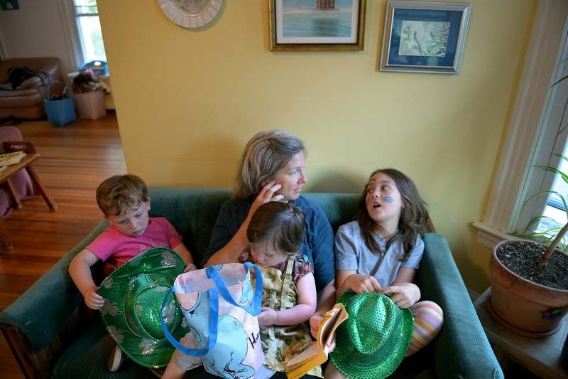 Frida Berrigan, center, discusses a passage she has just read from J.R.R. Tolkien's 'The Two Towers' with her stepdaughter Rosena Sheehan-Gaumer, 9, right, her son Seamus, 3, left, and daughter Madeline, 2, before dinner Thursday at the family's home in New London.  (Tim Cook/The Day)