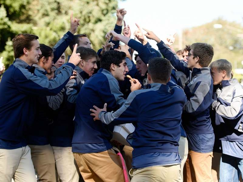 Members of the Westerly High School boys' soccer team race to get a piece of pizza from Pizza Lady on the corner of Liberty St. and Stillman Ave. during the annual Westerly/Pawcatuck Columbus Day Parade Monday, October 10, 2016. (Sean D. Elliot/The Day)