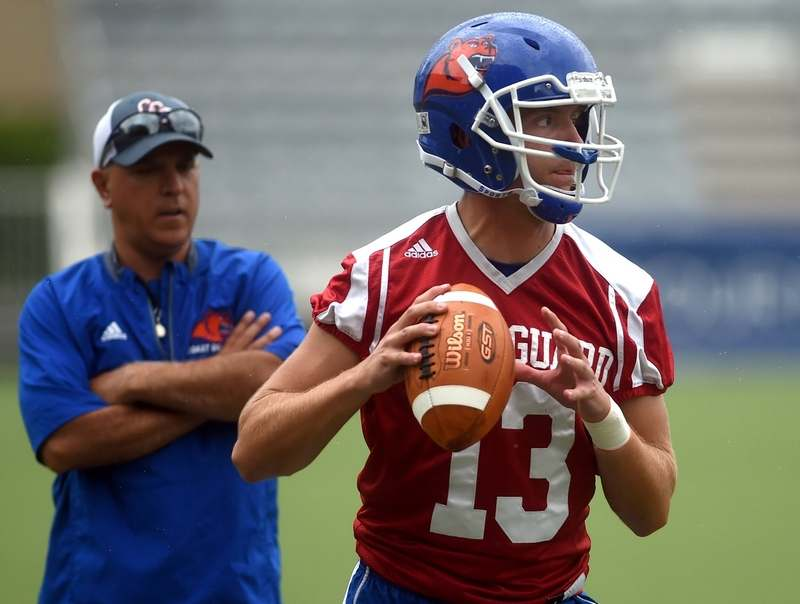 Coast Guard quarterback Ethan Goldcamp (13) participates during a drill under the close watch of offensive coordinator Ray LaForte, left, at practice on Aug. 7 in New London.  (Dana Jensen/The Day)