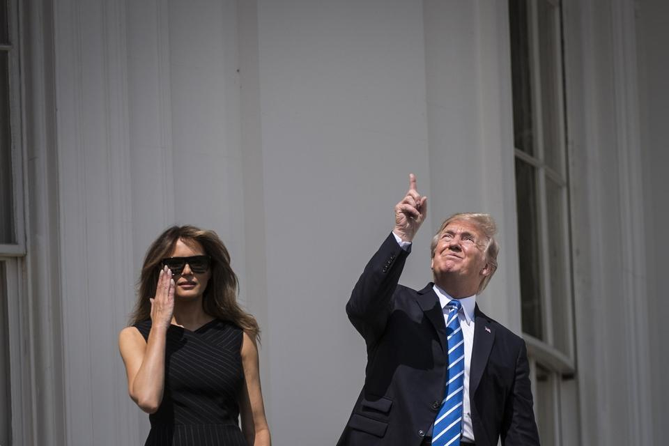 President Donald Trump looks up toward the solar eclipse, with first lady Melania Trump by his side, from a balcony at the White House. (Jabin Botsford/The Washington Post)