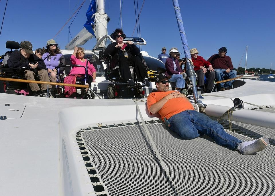 Bob Pfanner, center, of Niantic, enjoys a view from the net of a modified catamaran on Friday, Sept. 1, 2017, during a trip with the Impossible Dream. The nonprofit works with Shake A Leg Miami to provide adaptive sailing experiences to people with disabilities. (Sarah Gordon/The Day)