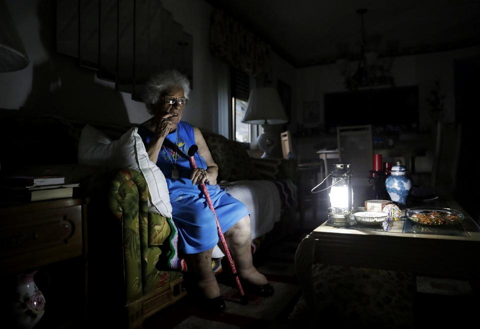 Mary Della Ratta, 94, sits by a battery powered lantern in her home three days after Hurricane Irma knocked out power in Naples, Fla., Wednesday, Sept. 13, 2017.