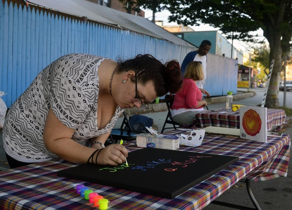 Faith Colter, a volunteer at Spark Makerspace, works on a community art project during a Park(ing) Day event on Friday, Sept. 15, 2017, along Eugene O'Neill Drive in New London.  Volunteers and Spark members turned two parking spaces into an art and game space for the evening as part of the national event.  (Sarah Gordon/The Day)