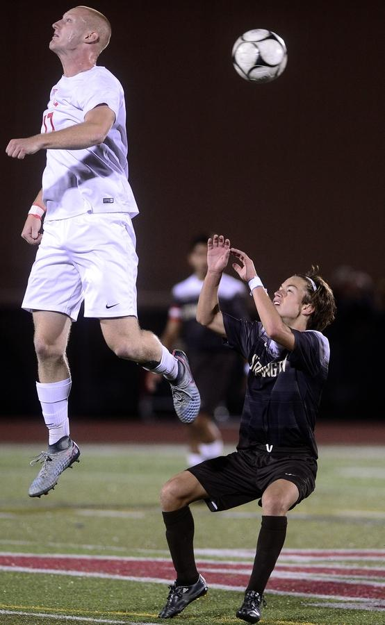 NFA's Alexander Jacobik leaps to head the ball past Stonington's Tyler Fidrych during Thursday night's boys' soccer game in Norwich where Stonington beate NFA 3-1. (Sarah Gordon/The Day)
