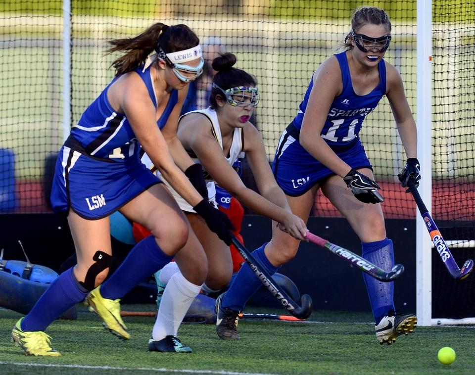 Stonington's Casey Boumenot, middle, attempts to move past Jenna Baron (11) and Samantha Chadwick (17) of Lewis Mills during a Class S state tournament field hockey game Thursday in Stonington.  Stonington won 8-0, getting four goals from Miranda Arruda, to advance to the semifinals for the second straight season. (Sarah Gordon/The Day)