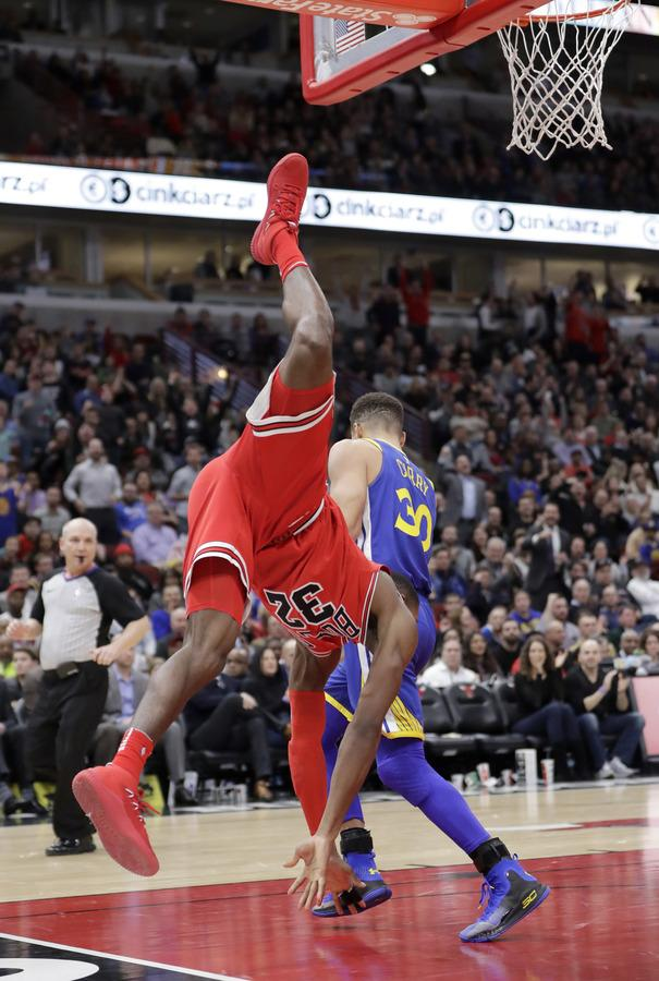 The Bulls' Kris Dunn of New London gets upside down after a dunk over Golden State's Stephen Curry during the second half of Wednesday's game in Chicago. The Warriors won 119-112. Dunn was injured on the play. (Charles Rex Arbogast/AP Photo)