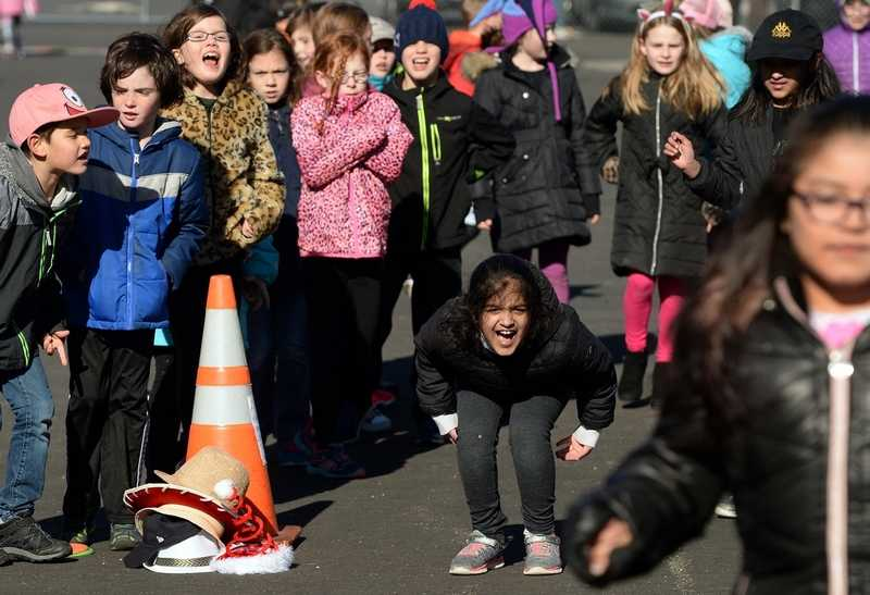 Deans Mill School third-grader Ajar Malik, center, and fellow third-graders cheer on their teammates while they participate in a relay race held by the student senators as an act of kindness during recess Thursday, Jan. 23, 2017.  The senators' act of kindness was to give their fellow students a fun outside activity at recess, since construction at the school has limited the activities available outdoors. The students at the school were trying to complete 50 acts of kindness this past week.  (Dana Jensen/The Day)