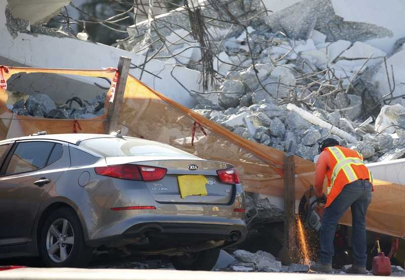 A worker uses a saw next to a crushed car under a section of a collapsed pedestrian bridge, Friday, March 16, 2018, near Florida International University in the Miami area.   The new pedestrian bridge that was under construction collapsed onto a busy Miami highway Thursday afternoon, crushing vehicles beneath massive slabs of concrete and steel, killing six people, authorities said.   (AP Photo/Wilfredo Lee)