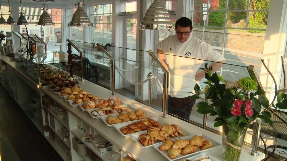 Adam Young, owner of Sift Bake Shop in Mystic, checks the pastry display before opening for the day at 7 a.m. May 26, 2016. He will be opening a second shop, at 102 Bay St. in Watch Hill. (Peter Huoppi/The Day)