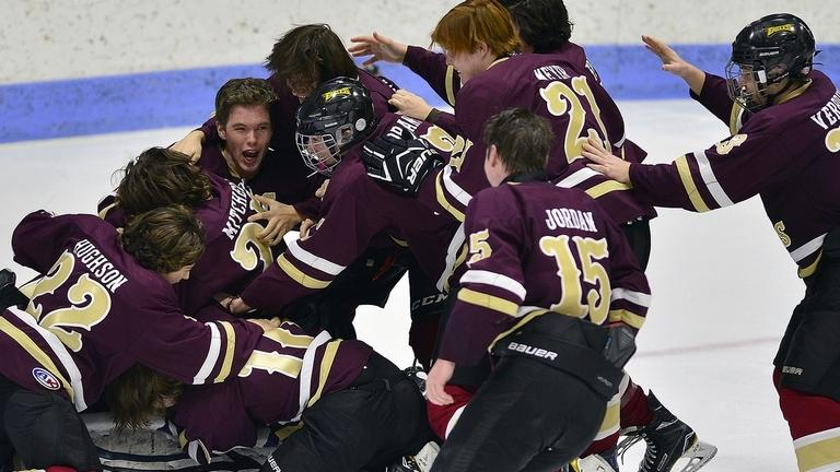Eastern Connecticut Eagles teammates pile on goalie Rylin Fowler after defeating Tri-Town 7-3 in the CIAC Division III hockey final on Saturday at Yale University's Ingalls Rink. It was the first title in program history for the Eagles, a cooperative program of eight local schools. (Sarah Gordon/The Day)