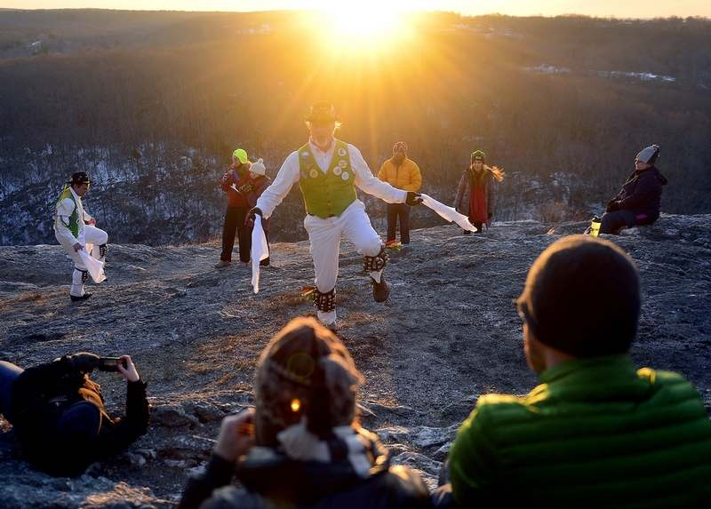 Spectators watch as the Westerly Morris Men mark the sunrise of the first day of spring on Tuesday, March 20, 2018, on top of Lantern Hill in North Stonington. The traditional English ritual dancing group was founded over 40 years ago and has been performing the rite of spring dances for more than 30 years. (Sarah Gordon/The Day)