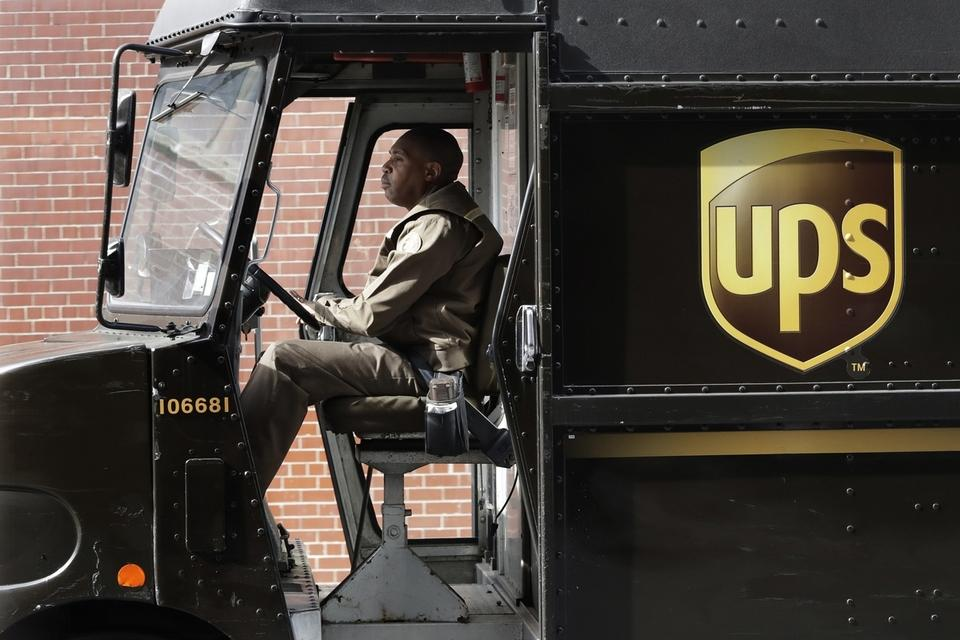 FILE - In this Tuesday, May 9, 2017, photo, a UPS driver takes his truck on a delivery route, in New York. UPS is adding a new charge of under $1 for shipments to residential customers during peak delivery periods in November and December.  (AP Photo/Mark Lennihan)