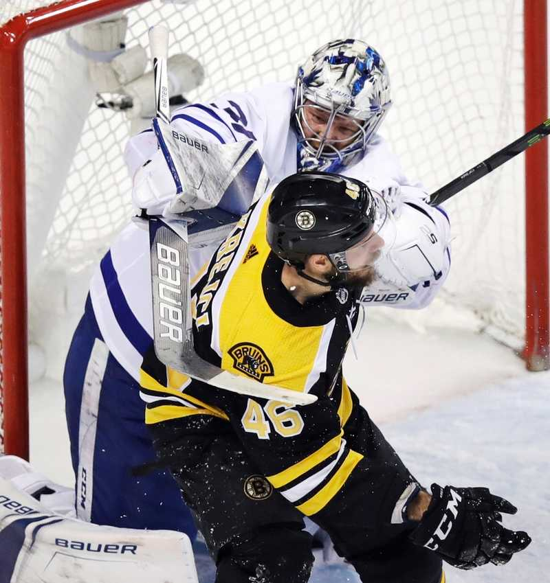 Toronto's Frederik Andersen, rear, hits Boston's David Krejci with his stick during the second period of Wednesday's game in Boston. (Charles Krupa/AP Photo)