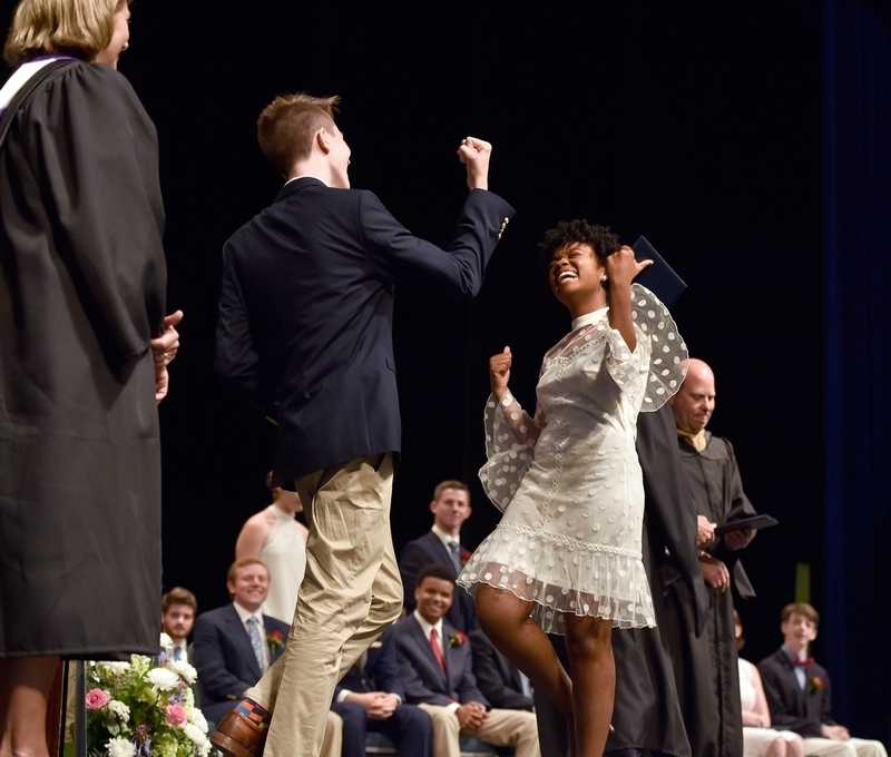 Colin Madaus, a graduating member of the Williams School's Class of 2018, performs a multi-step hand gesture with fellow graduate Asaada Craig after she received her diploma during the school's 127th commencement, held inside the Palmer Auditorium on the Connecticut College campus in New London on Wednesday, June 6, 2018. (Tim Martin/The Day)