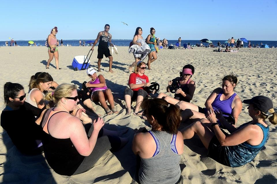 Beachgoers pause to watch participants in a Beach Body fitness class pass weights during a workout on Monday, July 9, 2018 at Ocean Beach in New London.  The class is offered through Renegade Fitness for members on Monday and Wednesday evenings at 5:45. (Sarah Gordon/The Day)