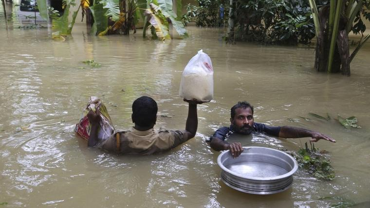 An Indian policeman, left, and a volunteer carry essential supplies for stranded people in a flooded area in Chengannur in the southern state of Kerala, India, Sunday, Aug.19, 2018. Some 800,000 people have been displaced and over 350 have died in the worst flooding in a century. (AP Photo/Aijaz Rahi)