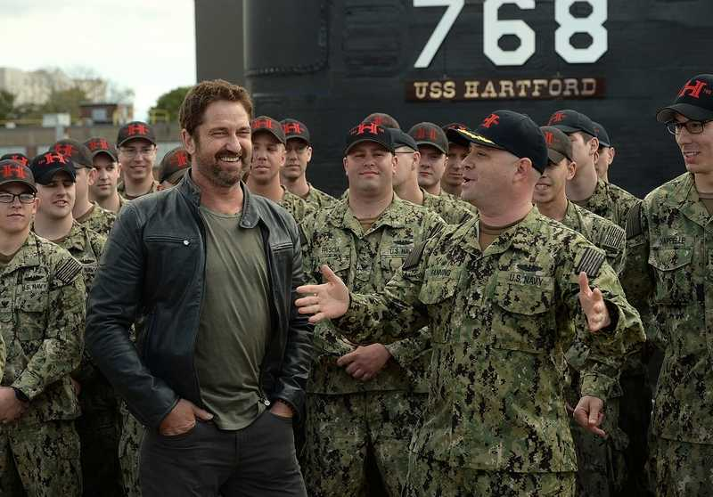 Actor Gerard Butler, left, chats with the USS Hartford's commanding officer, Cmdr. Matt Fanning, after posing for a photo with the crew of the Hartford (SSN 768) after attending the pier-side ceremony where the submarine crew was presented with the 2017 Battenberg Cup Award at the Naval Submarine Base in Groton on Saturday, Oct. 20, 2018. Butler was at the base for the advance screening of Lionsgate's