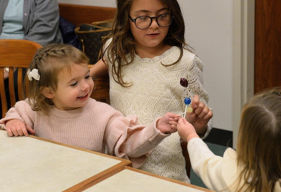 Wynnie, 3, left, and her sisters, Liora, 9, and , Joie, 2, tap their lollipops together and say 'cheers' while family members linger in the courtroom after Wynnie's adoption proceedings to join the family of Kaye-Leigh and Brian Doyle of East Lyme at Juvenile Court in Waterford on Friday, Nov. 16, 2018. The adoption was one of several that took place across the state as part of Adoption Day.  The girls' brother Gill, 2, not shown, also was at the table.  (Dana Jensen/The Day)