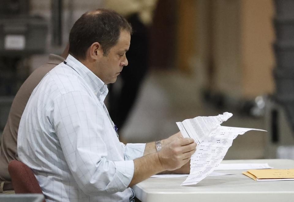 Employees look through damaged ballots at the Supervisor of Elections office during a recount, Thursday, Nov. 15, 2018, in West Palm Beach, Fla. (AP Photo/Wilfredo Lee)