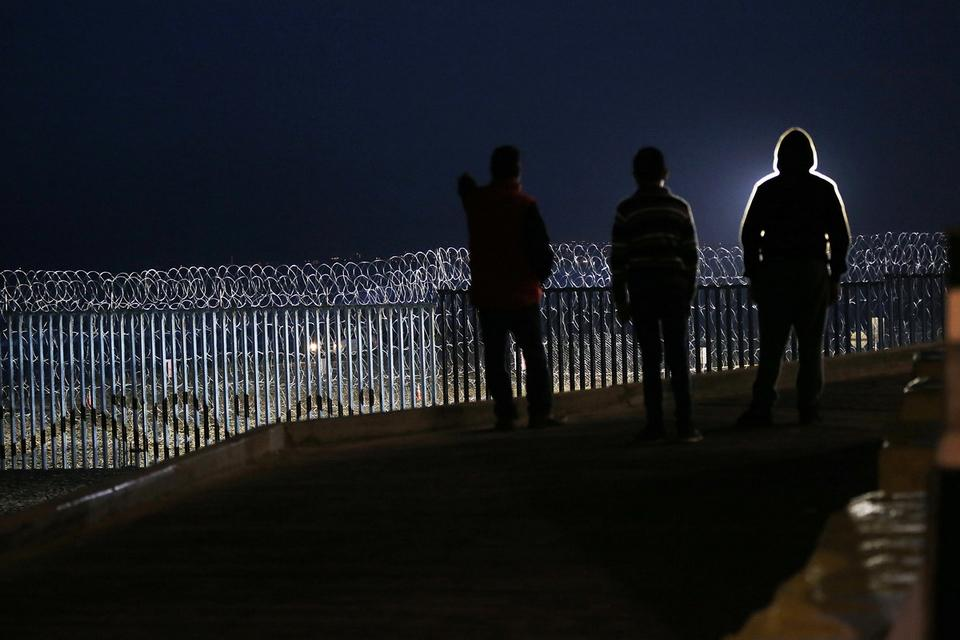 Residents stand on a hill before barriers, wrapped in concertina wire, separating Mexico and the United States, where the border meets the Pacific Ocean, in Tijuana, Mexico, Saturday, Nov. 17, 2018. Many of the nearly 3,000 migrants have reached the border with California. The mayor has called the migrants' arrival an 'avalanche' that the city is ill-prepared to handle. (AP Photo/Marco Ugarte)