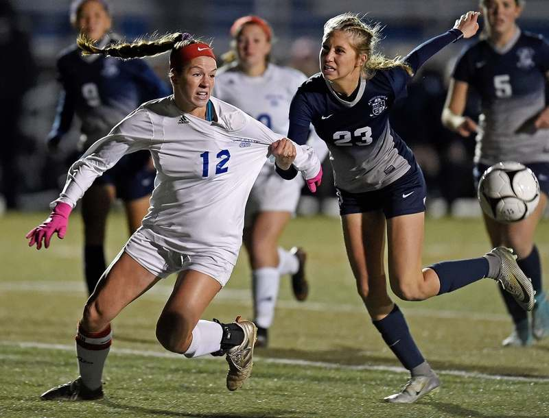 Old Lyme's Mya Johnson (12) fights to get free of Immaculate's Avery Jarbone (23) in the first half of the CIAC Class S girls' soccer tournament final on Sunday at Middletown High School. (Sean D. Elliot/The Day)