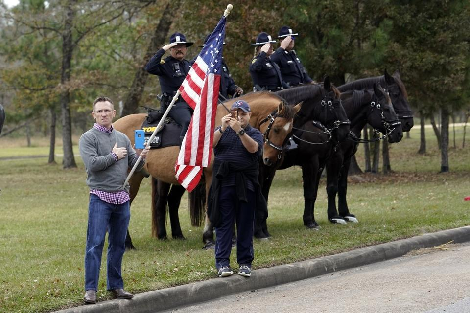 People line the road as the hearse carrying the flag-draped casket of former President George H.W. Bush heads to the Union Pacific train facility Thursday, Dec. 6, 2018, in Houston. (AP Photo/David J. Phillip, Pool)