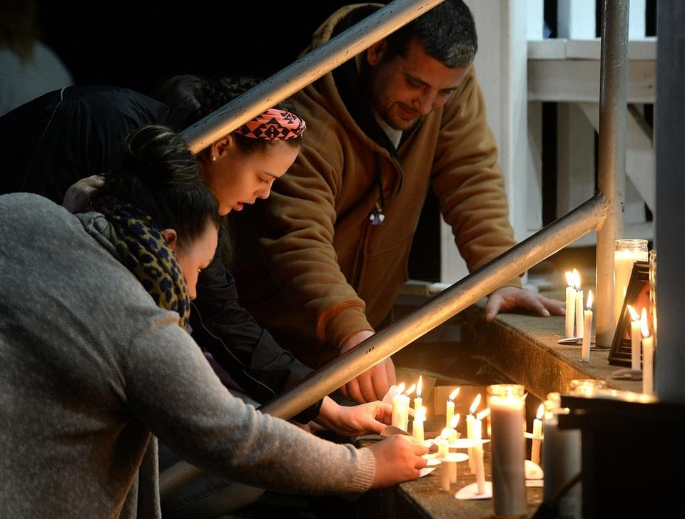 People place candles near two photographs of Corina Zukowski on the steps of the gazebo after a candlelight vigil Friday, Dec. 14, 2018, at Civic Triangle Park in Waterford. Zukowski who was fatally stabbed Monday night.  (Dana Jensen/The Day)
