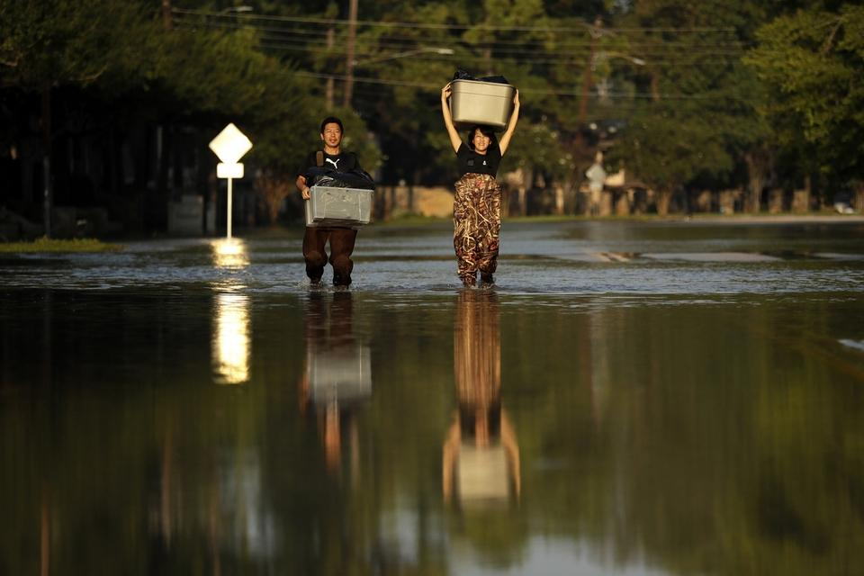 FILE - In this Monday, Sept. 4, 2017 file photo, Mariko Shimmi, right, helps carry items out of the home of Ken Tani in a neighborhood still flooded from Harvey in Houston. Some neighborhoods around Houston remain flooded and thousands of people have been displaced by torrential rains and catastrophic flooding since Harvey slammed into Southeast Texas last week. According to a scientific report from the United Nations released on Wednesday, March 13, 2019, climate change, a global major extinction of animals and plants, a human population soaring toward 10 billion, degraded land, polluted air, and plastics, pesticides and hormone-changing chemicals in the water are making the planet an increasing unhealthy place for people. (AP Photo/Gregory Bull)