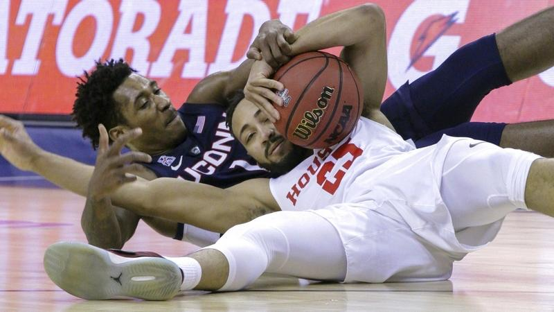 UConn's Christian Vital and Houston's Galen Robinson Jr. scramble for a loose ball during the first half of Friday's American Athletic Conference tournament quarterfinal game in Memphis, Tenn. The top-seeded Cougars ended UConn's season with an 84-45 victory over the No. 9 Huskies. (AP Photo/Troy Glasgow)