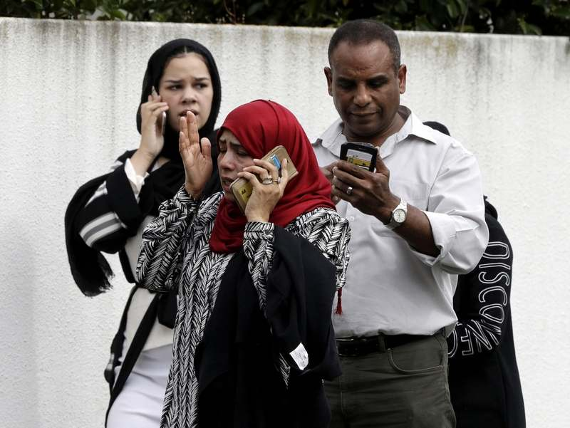 In this March 15, 2019, file photo, people wait outside a mosque in central Christchurch, New Zealand. The gunman who attacked two mosques in New Zealand, killing at least 50 people, was said to have been inspired by the man who in 2015 killed nine black worshippers at a church in Charleston, S.C. (AP Photo/Mark Baker, File)