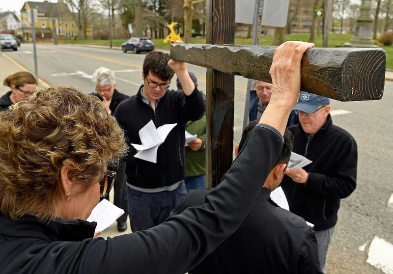 Mary White, left, reaches out to touch the cross on Good Friday, April 19, 2019, as the Rev. Ranjit K. Mathews of St. James Episcopal Church in New London leads worshippers in walking the Stations of the Cross in New London. The procession stopped at nine downtown locations, rather than the traditional 14, where either violence or injustice was inflicted or where violence and injustice are addressed. Members of the group took turns carrying the cross and reading prayers at each station. They sang
