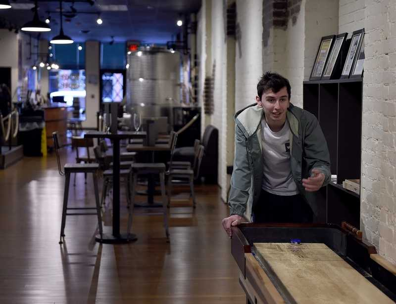 Robert Thewissen plays shuffleboard with friend Tim O'Reilly, not pictured,  on Thursday, April 18 at Tapped Apple Cider & Winery in downtown Westerly. (Sarah Gordon/The Day)