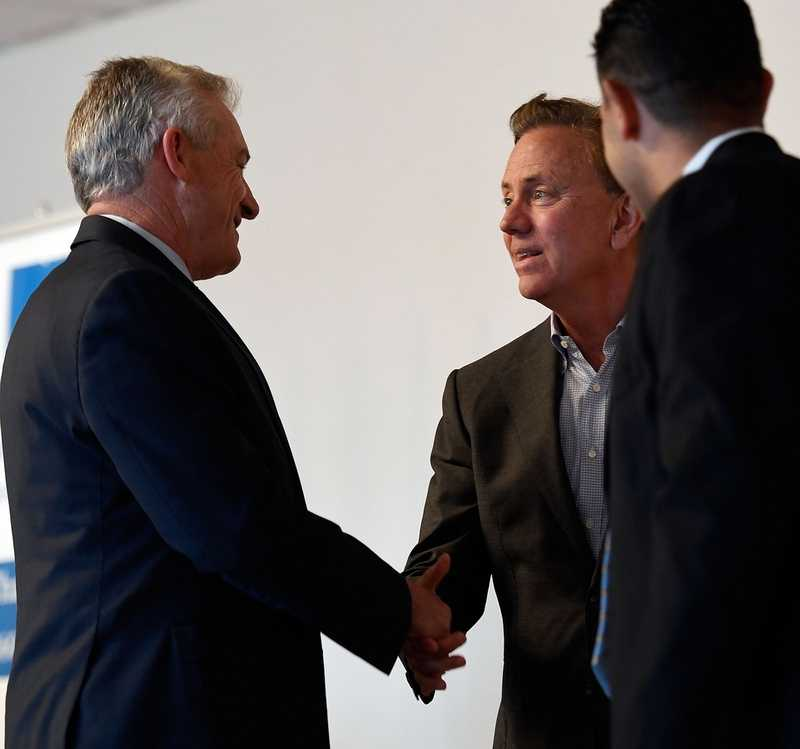 Gov. Ned Lamont greets Len Wolman of The Waterford Group, left, and Rodney Butler, chairman of the Mashantucket Pequot Tribe, as he arrives to address members of the Chamber of Commerce of Eastern Connecticut at a luncheon Thursday, April 25, 2019, at Ocean Beach Park's Port 'N Starboard banquet hall. Lamont offered remarks on his first 100 days in office and took questions from the members.  (Sean D. Elliot/The Day)