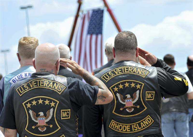 Members of the U.S. Veterans Motorcycle Club salute the flag during the playing of the national anthem at the beginning of a memorial and remembrance service for seven motorcyclists and their spouses who died in the June crash Saturday, July 13, 2019, in the parking lot of Gillette Stadium in Foxborough, Mass.  The seven bikers were killed when a pickup truck hauling a flatbed trailer slammed into a group of riders in Randolph, N.H.  (Mark Stockwell/The Sun Chronicle via AP)