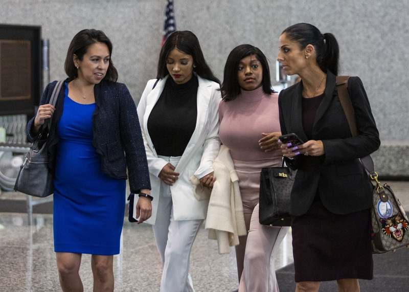 Joycelyn Savage, second from left, and Azriel Clary, second from right, women who lived with R&B singer R. Kelly, walk into Dirksen Federal Courthouse for Kelly's hearing with attorney Gloria Schmidt, left, another attorney, Tuesday afternoon, July 16, 2019. Kelly is expected to appear on charges that he recruited girls and women to have illegal sex with him and then covered up the crimes by paying and threatening the victims and witnesses. (Ashlee Rezin/Sun-Times/Chicago Sun-Times via AP)