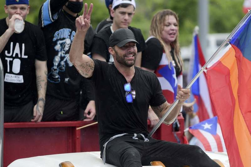 Puerto Rican singer Ricky Martin holds a gay pride flag as he participates in a protest demanding the resignation of Gov. Ricardo Rossello in San Juan, Puerto Rico, Monday, July 22, 2019. Protesters are demanding Rossello step down for his involvement in a private chat in which he used profanities to describe an ex-New York City councilwoman and a federal control board overseeing the island's finance. (AP Photo/Carlos Giusti)