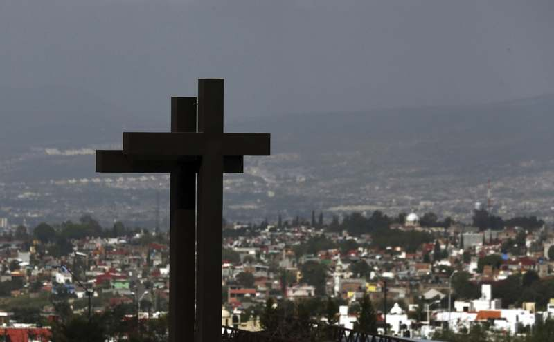 Crosses tower over the city of Morelia, Michoacan state, Mexico, Tuesday, Oct. 15, 2019, where families of 13 Mexican police officers killed in an apparent cartel ambush are gathering at a funeral home, many of them angry at the government and police chiefs they believe sent them to a certain death. (AP Photo/Marco Ugarte)