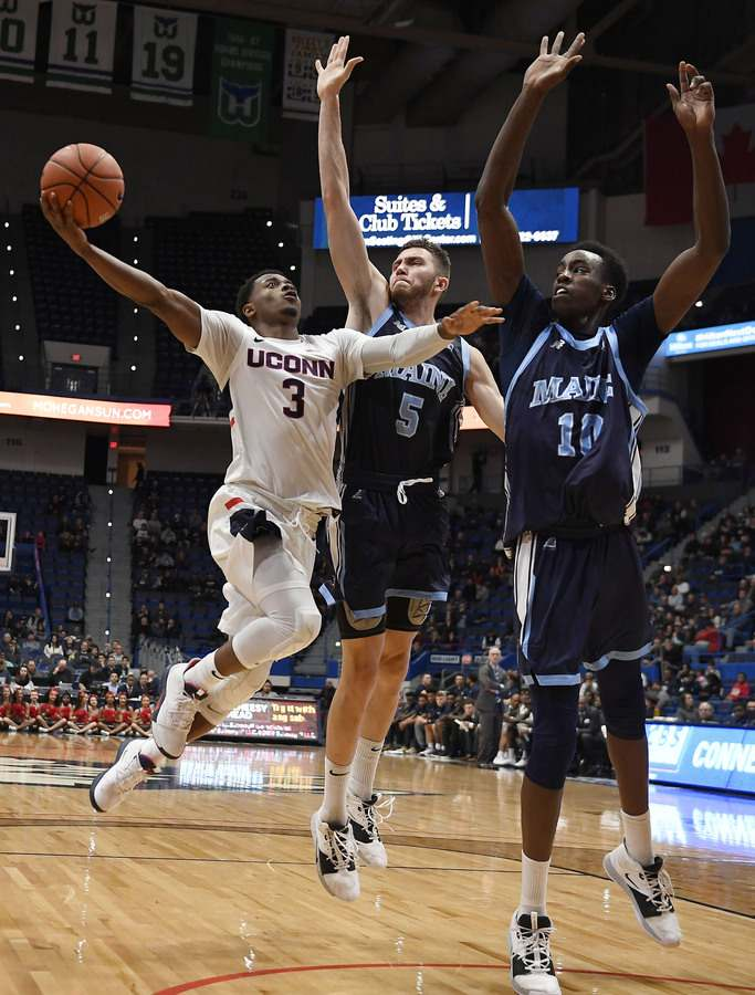 UConn's Alterique Gilbert drives to the basket against Maine's Nedeljko Prijovic, center, and Stephane Ingo during Sunday's game in Hartford. (AP Photo/Jessica Hill)