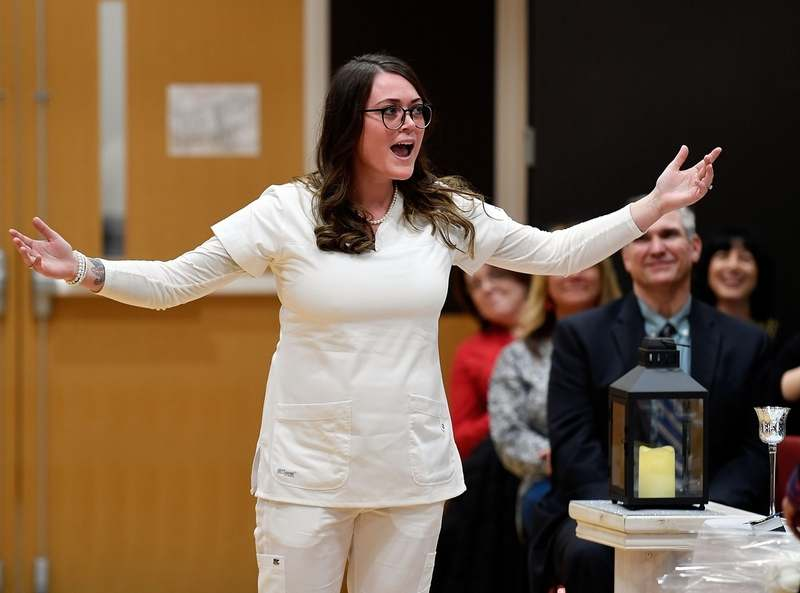 Kelsey Durand feigns outrage as she steps forward just as the faculty presenting graduates with the nursing pins switch during graduation for the 54th class in the Associate Degree Nursing Program at Three Rivers Community College Friday, December 13, 2019 in the college's multi-purpose room. Durand stepped forward, got a hug from the faculty members who had just finished presenting pins, and then watched as that faculty member returned to her seat to make way for the faculty member who would present Durand with her pin.  (Sean D. Elliot/The Day)