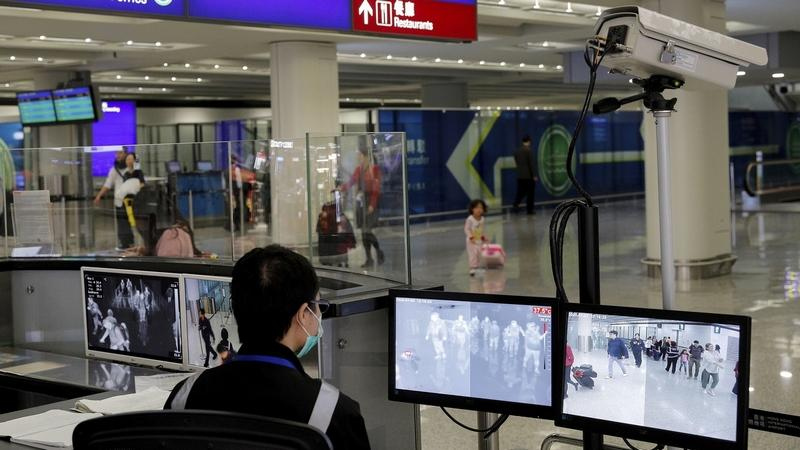 In this Jan. 4, 2020, file photo, a health surveillance officer monitors passengers arriving at the Hong Kong International airport in Hong Kong. On Friday, Jan. 17, 2020, the U.S. Centers for Disease Control and Prevention officials said they will begin screening airline passengers at three U.S. airports who traveled from Wuhan in central China, for a new illness that has prompted worries about a new international outbreak. (AP Photo/Andy Wong, File)