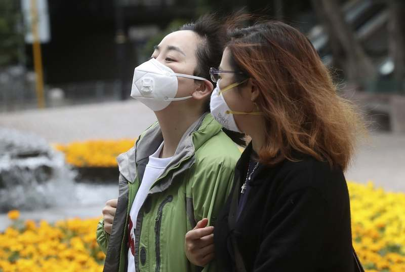 People wear masks in Hong Kong, Sunday, Jan. 26, 2020. The new virus accelerated its spread in China and the U.S. Consulate in the epicenter of the outbreak, the central city of Wuhan, announced Sunday it will evacuate its personnel and some private citizens aboard a charter flight. (AP Photo/Achmad Ibrahim)