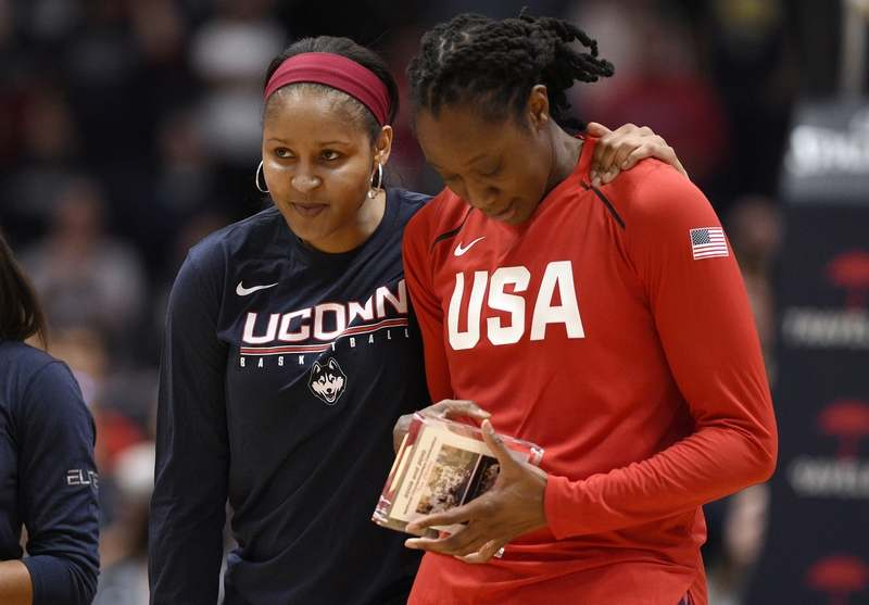 Minnesota Lynx and former UConn player Maya Moore, left, puts her arm around former UConn teammate and New York Liberty player Tina Charles during a ceremony honoring their championship team before an exhibition basketball game between UConn and the United States, Monday, Jan. 27, 2020, in Hartford, Conn. (AP Photo/Jessica Hill)
