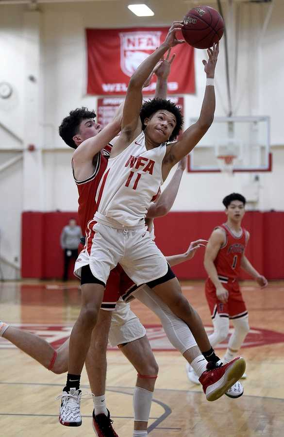 NFA's Jared Martin (11) pulls down a rebound over Fitch's Seamus Greaves (15) during a boys basketball game on Tuesday, February 11, 2020 at Norwich Free Academy. (Sarah Gordon/The Day)