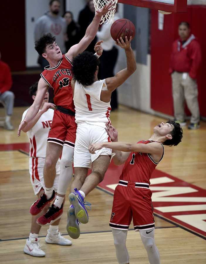 Fitch's Seamus Greaves (15) and Adriel Atad (1) block a shot from NFA's Xavier Marquez (1) during a boys basketball game on Tuesday, February 11, 2020 at Norwich Free Academy. (Sarah Gordon/The Day)