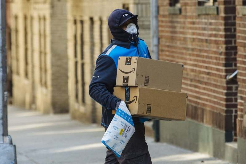 A worker wearing a protective mask and gloves carries Amazon boxes during a delivery in the Bronx borough of New York on Thursday, March 26, 2020. (Bloomberg photo by Angus Mordant)