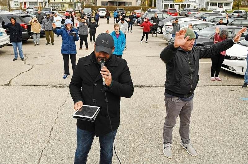 Pastor Joel Rivera, front left, of Get Wrapped Church in New London, and Pastor Adam Bowles of Castle Church in Norwich, right, gather with members of their congregations for a community prayer Friday, April 3, 2020, in the parking lot of Backus Hospital in Norwich.  (Sean D. Elliot/The Day)