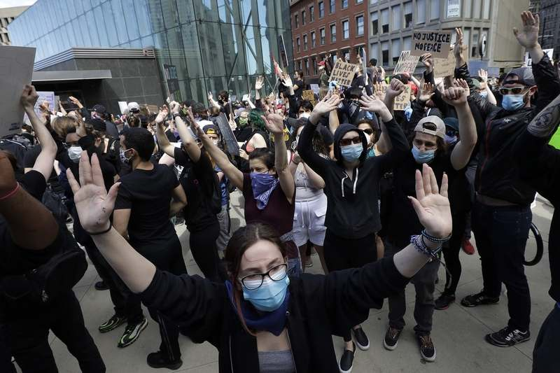 Protesters demonstrate in Boston, Sunday, May 31, 2020, over the death of George Floyd who died after being restrained by Minneapolis police officers on May 25. (AP Photo/Steven Senne)