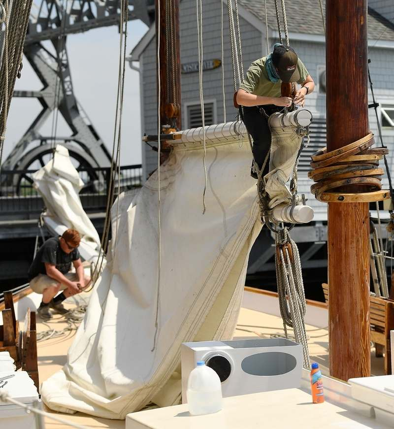 Tina Doran, right, rigs the foresail as Jack Meyer works on the jib sail Wednesday, June 3, 2020, on the Argia in preparation for their shortened summer sailing season.  (Sean D. Elliot/The Day)