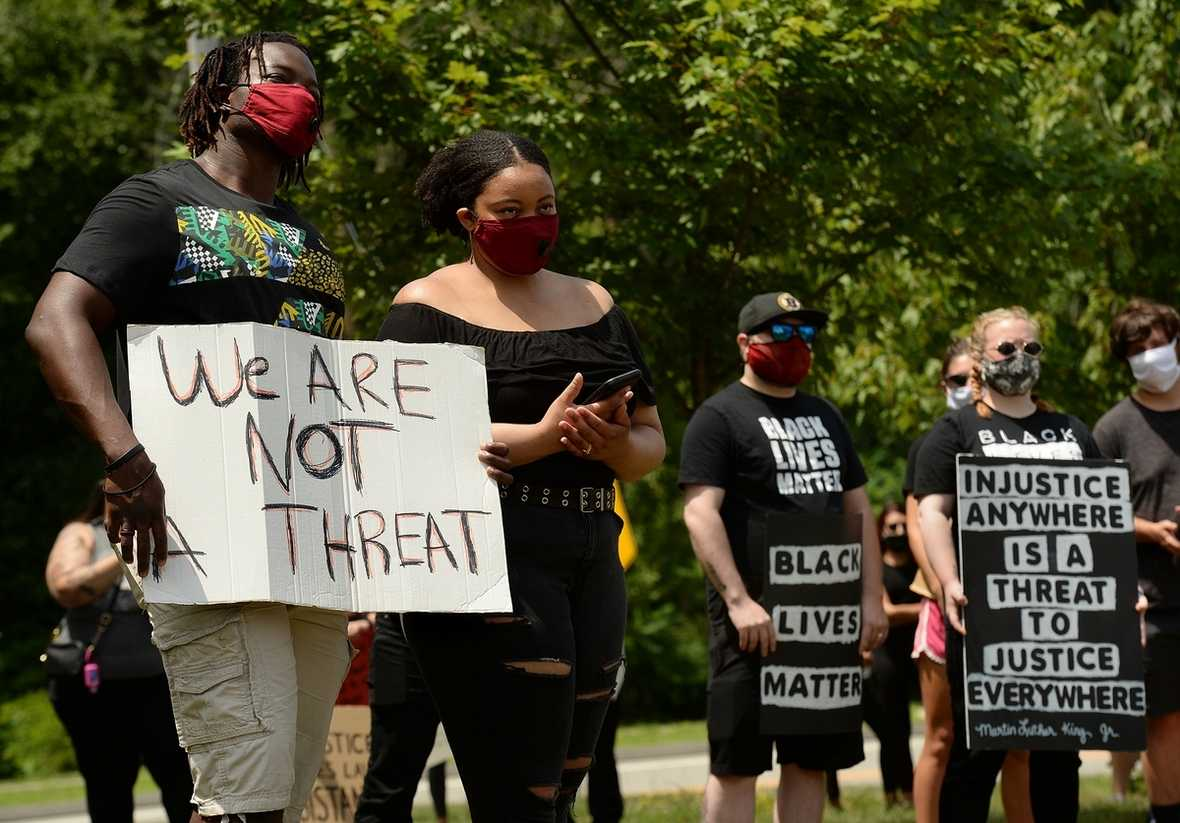 Jimmy Eugene, left, and Moriya Phillips, of Norwich, and others listen to one of the speakers Saturday, July 4, 2020, during the Black Lives Matter event on the Ledyard green.  Later the group marched to the Ledyard Police Department.  (Dana Jensen/The Day)